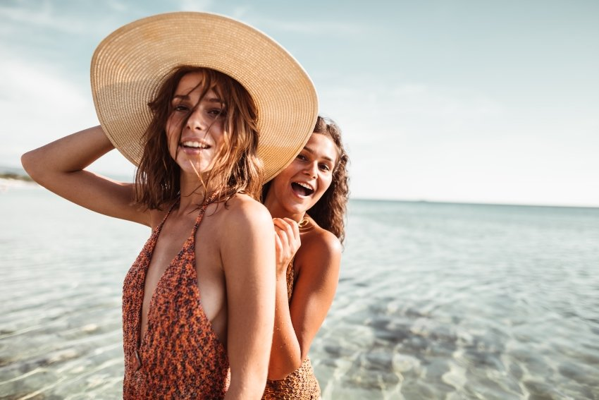 Two girls at the beach having fun in the water.