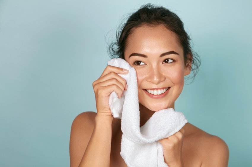 Young woman holding a towel after washing her face.